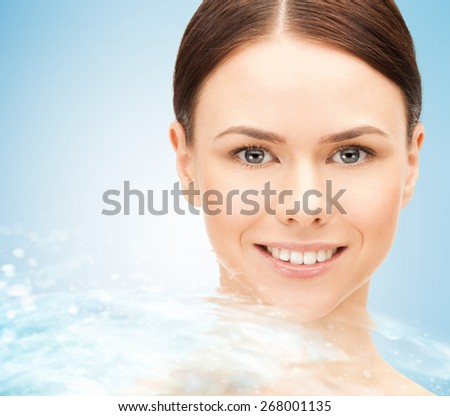 beauty, people, freshness, purity and health concept - face of beautiful young woman and water splash over blue background - stock photo