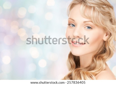 beauty, people, hair care and health concept - beautiful young woman face with long wavy hair over blue lights background - stock photo