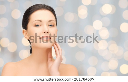 beauty, people, holidays, luxury and health concept - beautiful young woman touching her face over lights background - stock photo