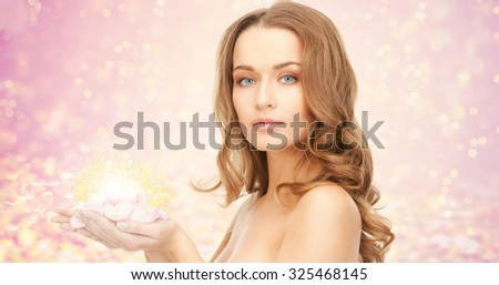 beauty, people, holidays, skin and body care concept - beautiful young woman with rose flower petals and bare shoulders over pink lights background - stock photo