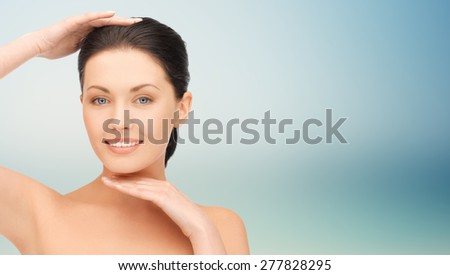beauty, people, plastic surgery and health concept - beautiful young woman touching her face and chin over blue background - stock photo