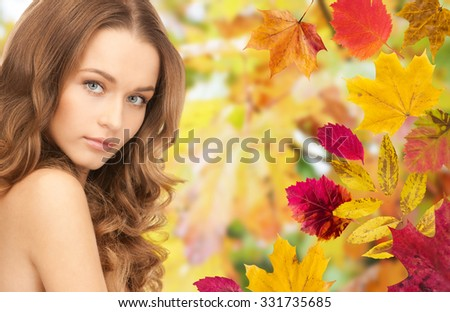 beauty, people, season and health concept - beautiful young woman face with long curly hair over autumn leaves background - stock photo