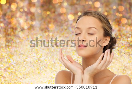 beauty, people, skincare and health concept - young woman face and hands over holidays lights background - stock photo