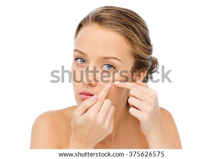 beauty, people, skincare and health concept - young woman squeezing pimple on her face - stock photo