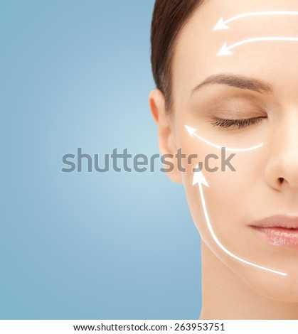 beauty, people, skincare and plastic surgery concept - beautiful young woman face with facelift marks over blue background - stock photo