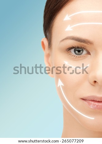 beauty, people, skincare and plastic surgery concept - beautiful young woman face with facelift marks over blue background