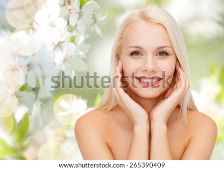 beauty, people, summer, spring and health concept - beautiful young woman touching her face over green blooming garden background - stock photo
