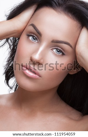 Beauty picture of a young pretty woman holding her hair with hands - stock photo
