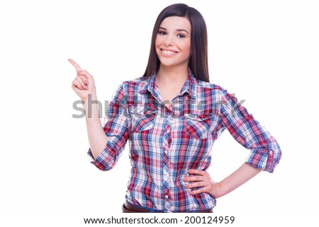 Beauty pointing copy space. Beautiful young smiling woman pointing copy space and holding hand on hip while standing isolated on white - stock photo
