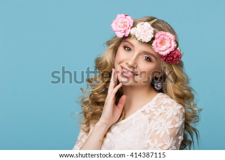 Beauty portrait. Beautiful blonde woman with wreath of flowers. Looking at camera. Touching hair. Isolated on blue background. Youth, happiness concept - stock photo