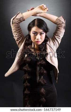 Beauty Portrait. Beautiful brunette Asian woman with long black hair. Shot in a studio on a black background