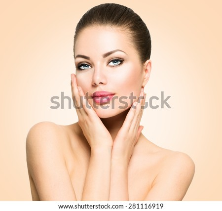 Beauty Portrait. Beautiful Spa Woman Touching her Face. Perfect Fresh Skin. Beauty brunette Model. Youth and Skin Care Concept. Studio shot over beige background - stock photo
