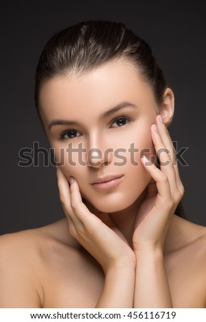 Beauty Portrait. Beautiful Spa Woman Touching her Face. Perfect Fresh Skin. Beauty brunette Model. Youth and Skin Care Concept. Studio shot. Isolated on gray background - stock photo