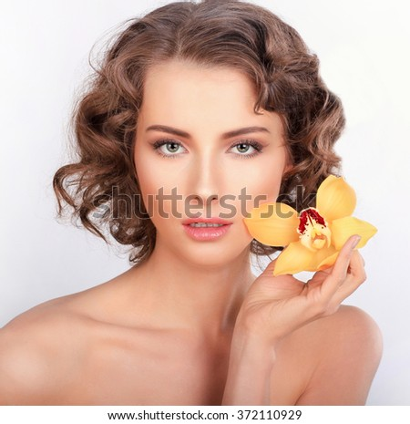 Beauty portrait. Beautiful stylish girl with yellow orchid flower. Isolated on a white background - stock photo