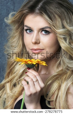 Beauty Portrait. Beautiful Woman with flower. Perfect Fresh Skin. On blue Background. Pure Beauty Model. Youth and Skin Care Concept - stock photo