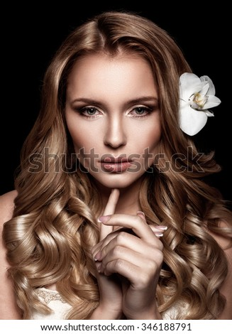 Beauty Portrait. Beautiful Woman with wavy hair touching her face. Perfect Fresh Skin. Pure Beauty Model. Youth and Skin Care Concept.