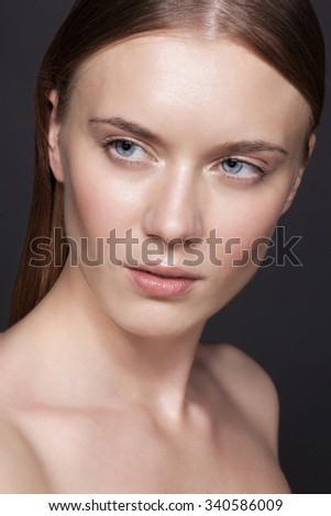 Beauty portrait closeup of a young attractive charming sensual woman with dark hair, perfect shiny clean skin, nude daily fresh makeup and blue eyes, looking at camera. - stock photo