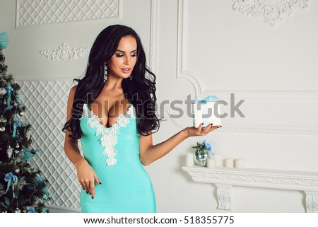 Beauty portrait in Christmas. Christmas beauty girl. The girl in the blue dress gives a gift for Christmas. The girl gives a gift.