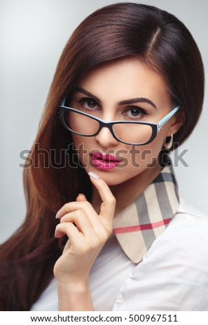 Beauty portrait of a beautiful brunette woman wearing glasses isolated on a gray background.