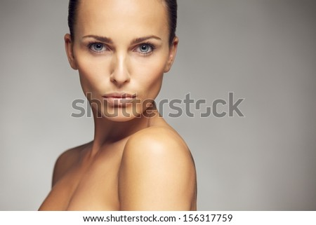 Beauty portrait of a beautiful caucasian young woman with perfect face skin isolated against gray background - stock photo