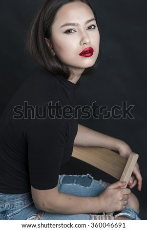 Beauty portrait of a beautiful feminine Asian brunette with long hair in a studio on a background in a black sweater sits on a chair leaning sideways