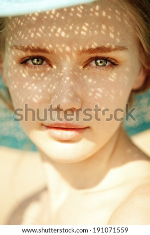 Beauty portrait of a beautiful woman in hat close-up. Beauty portrait of a trendy girl with rays of the sun on her face - stock photo