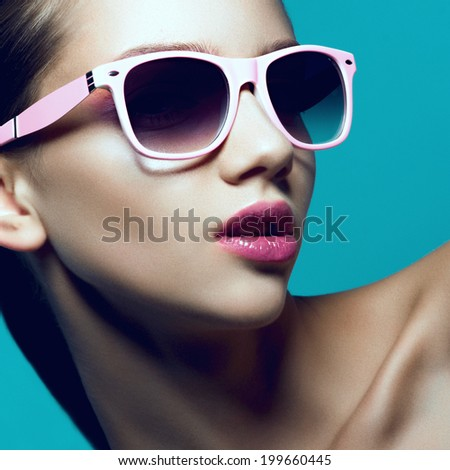 Beauty portrait of a beautiful young girl in studio with pink sunglasses on a blue background, close up