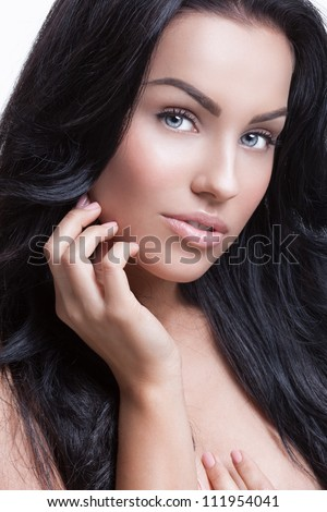 Beauty portrait of a beautiful young lady holding her hand on the face - stock photo
