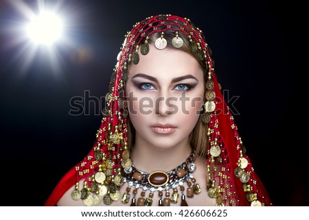 Beauty portrait of a beautiful young woman girl lady model, beige lips and black smoky eyes. Professional makeup studio. Traditional oriental style red wrap with golden coins. New horizontal photo