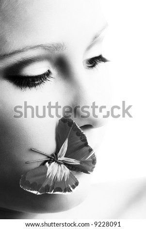 beauty portrait of a beautiful young woman with a butterfly on her lipps