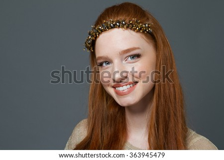 Beauty portrait of a cheerful redhead woman looking at camera over gray background - stock photo