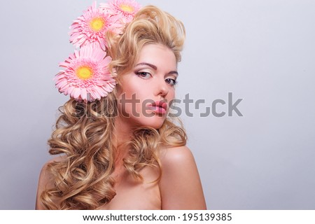 BEAUTY portrait of a girl with pink flowers in her hair. Portrait of blonde hair with volume. Professional make-up - stock photo