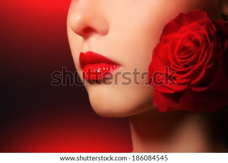beauty portrait of a girl with red rose on black background