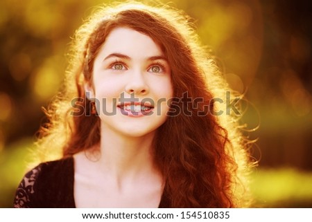 Beauty portrait of a gorgeous young woman with windblown hair in nature.   - stock photo