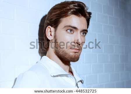 Beauty portrait of a handsome pensive young man standing by a white brick wall. Men's beauty, fashion. - stock photo