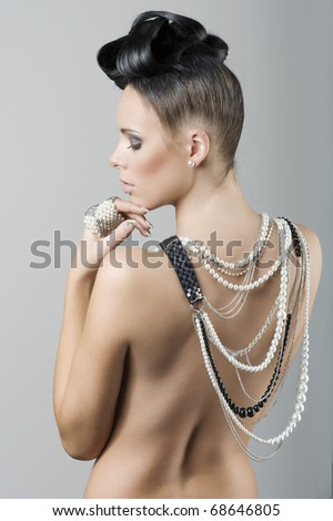 beauty portrait of a naked brunette with creative hair style and covering her back with jewellery - stock photo