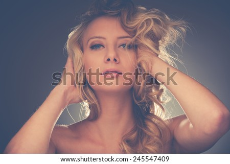 Beauty portrait of a pretty caucasian woman with blond hair over grey - stock photo