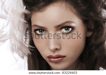 beauty portrait of a pretty girl with big grey eyes wearing a soft pink feather accessory in her hair - stock photo