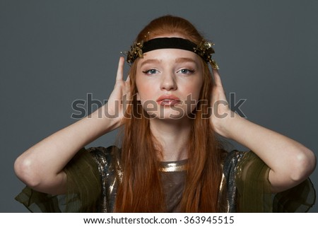 Beauty portrait of a pretty redhead woman posing over gray background - stock photo