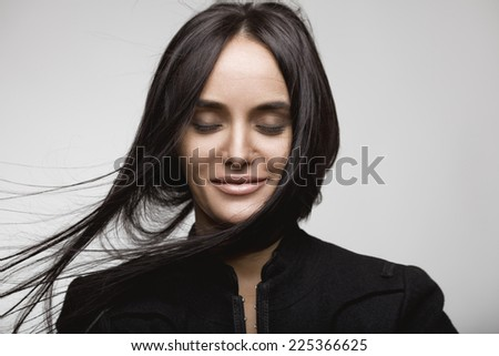 Beauty portrait of a smiling brunette girl with flying hair. Magnificent hair. - stock photo
