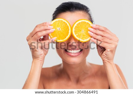 Beauty portrait of a smiling woman covering her eyes with orange isolated on a white background - stock photo