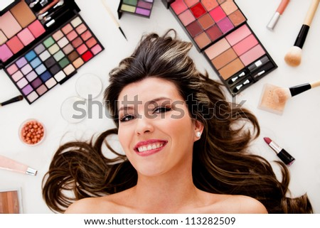 Beauty portrait of a woman lying on the floor with makeup - stock photo