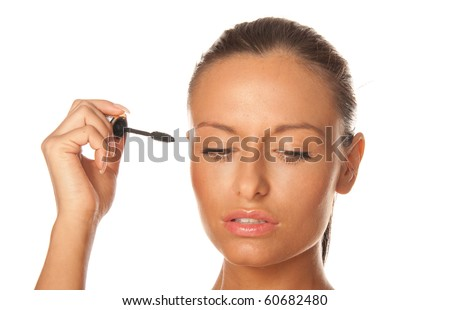 Beauty portrait of a young and attractive woman applying mascara isolated on white background - stock photo