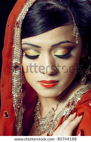 Beauty portrait of a young indian woman in traditional clothing with bridal makeup and jewelry, closeup shot