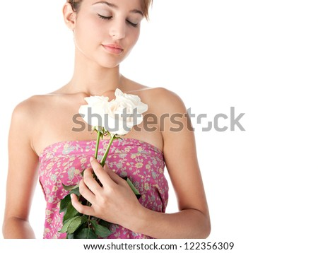 Beauty portrait of a young woman holding three perfectly shaped white roses, isolated on a white background.