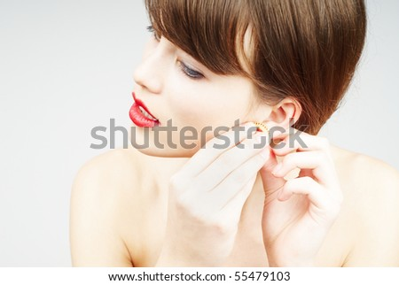 beauty portrait of a young woman putting an earring - stock photo