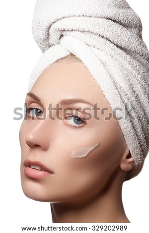 Beauty portrait of a young woman with beautiful healthy person, studio shot attractive girl on a white background, causing a scrub on face. Peeling face. Beautiful girl in a towel on her head - stock photo