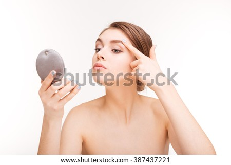 Beauty portrait of a young woman with fresh skin holding mirror isolated on a white background