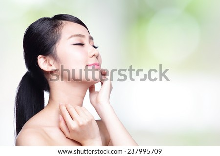 beauty portrait of a young woman with hand on her shoulder isolated on nature green background, concept for health , asian beauty model