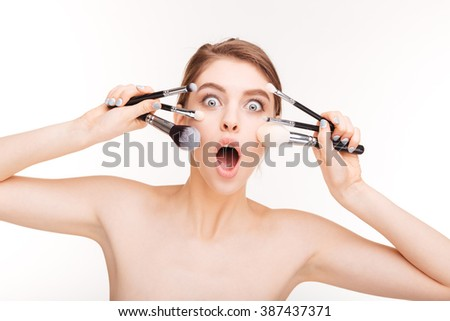 Beauty portrait of amazed funny young woman with makeup brushes over white background - stock photo